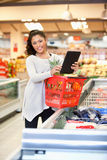 Shopper in store using digital tablet Stock Photography