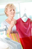 Shopper with tanktop. Portrait of middle aged woman choosing new tanktop in clothing departmant Stock Image