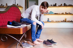 Shopper is thinking about shoes. Shopper is thinking about what shoes to buy royalty free stock photo