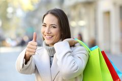 Shopper with thumbs up holding shopping bags in winter. Happy shopper with thumbs up holding shopping bags in winter in the street stock photography