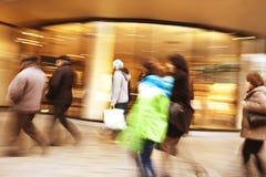 Shopper walking in front of shop window Stock Image