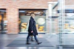 A shopper walking in front of shop window Royalty Free Stock Photo