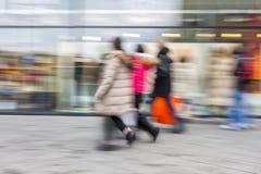 A shopper walking in front of shop window Stock Image
