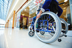 Shopper in wheelchair. Disabled shopper moving in wheelchair along departments in the mall stock image