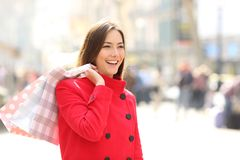 Shopper in winter walking and holding shopping bags. Happy shopper in winter walking and holding shopping bags in the street royalty free stock photos