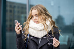 Shopper woman buying online on the smart phone in the street Stock Images