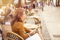 Shopper woman hand shopping with a smart phone and carrying bags royalty free stock photography