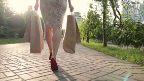 Shopper woman legs with shopping bags in street stock video footage