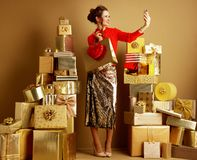 Shopper woman with shopping bag and red heart taking selfie with. Full length portrait of happy trendy shopper woman in red blouse and golden sparkly sequin stock photography
