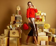 Shopper woman with shopping bag and red heart using a cell phone stock photo