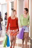 Shoppers chatting. Photo of happy girls walking down trade center and chatting stock image