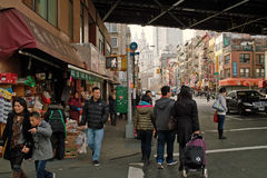 Shoppers in Chinatown New York USA 2013. Looking West down East Broadway where Manhattan Bridge passes over it and Market Street crosses it. Chinatown, Manhattan royalty free stock photo