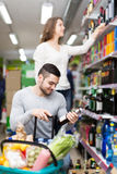 Shoppers choosing bottle of wine at liquor store Royalty Free Stock Photography