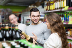 Shoppers choosing bottle of wine at liquor store Stock Images