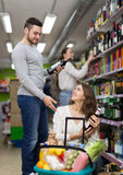 Shoppers choosing bottle of wine at liquor store Royalty Free Stock Photo