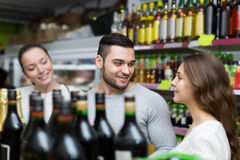 Shoppers choosing bottle of wine at liquor store Stock Photography