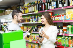 Shoppers choosing bottle of wine at liquor store Royalty Free Stock Images