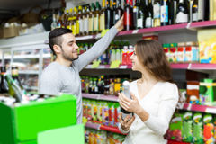 Shoppers choosing bottle of wine at liquor store Royalty Free Stock Photos