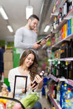 Shoppers choosing bottle of wine at liquor store Stock Photos