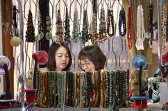 Shoppers choosing the necklace before buying it Royalty Free Stock Photos