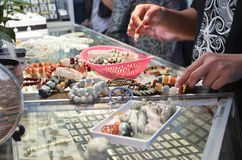 Shoppers choosing the necklace before buying it Royalty Free Stock Images