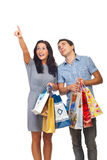 Shoppers couple pointing and looking up. Young couple holding shopping bags ,woman pointing and both looking up isolated on white background Stock Photo