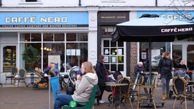 Shoppers And Families Relaxing And Sitting Outside A Caffe Nero Coffee Shop