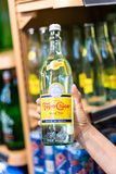 Shoppers hand holding a bottle of topo chico. Brand mineral sparking water in a supermarket aisle royalty free stock photography