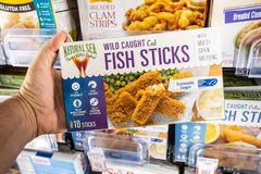 Shoppers hand holding a package of Natural Sea  brandwild caught cod fish sticks