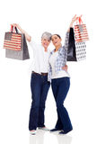 Shoppers holding purchases. Happy shoppers holding purchases over white background Stock Image
