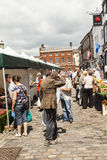 Shoppers at Leek's open air market. Leek, Staffordshire Moorlands, England, U.K - June 21 2014 : Shoppers at Leek's open air market With down at heal man in Royalty Free Stock Photography