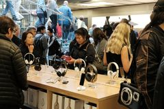 Shoppers and members of the public seen in a well-known retail store, trying headphones and other related accessories. royalty free stock image