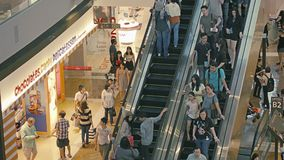 Shoppers are moving on the floors and escalators