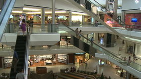 Shoppers moving through mall on escalators. A view or scene of Shopping stock footage