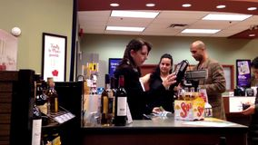 Shoppers paying wine inside liquor store stock video