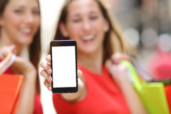 Shoppers showing a blank smart phone screen. Two joyful shoppers with shopping bags showing a blank smart phone screen in the street Royalty Free Stock Image