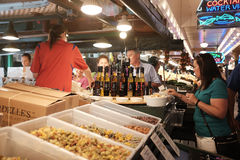 Shoppers study cooking oil varieties at pasta booth at Pike Place Market Seattle WA Royalty Free Stock Image