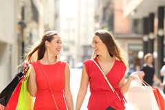 Shoppers talking holding shopping bags. Front view of two fashion happy shoppers in red talking holding shopping bags in the street stock photos