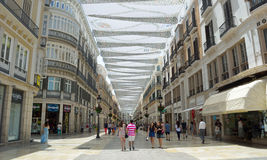 Shoppers under canopy covered pedestrian shopping street in Malaga city centre. Stock Photography