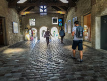 Shoppers walk through stone arcade at Bercy Village in Paris Stock Photos
