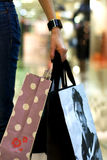 Shopping. Woman hand holding shopping bags on background of shopping center Stock Image