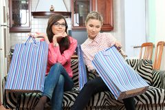 After shopping. Portrait of young women sitting at home with bags after shopping stock photos