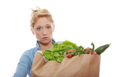 Shopping. Young woman holding a grocery bag full of fresh and healthy food isolated on white background Royalty Free Stock Photos