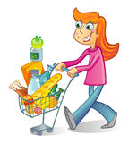 Shopping. A woman pushing a basket while shopping in the grocery store Stock Photography