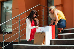 Two young fashion women with shopping bags on the mall steps Royalty Free Stock Photo