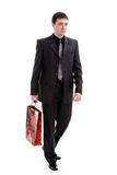 Shopping. A young man in a suit comes with a bag in his hands, isolated on a white background Royalty Free Stock Photography