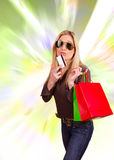 Shopping. Happy blond woman with shopping bags and credit card on abstract shapes background Stock Photos