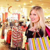 Shopping. Happy blond woman with shopping bags in shopping center Royalty Free Stock Photo