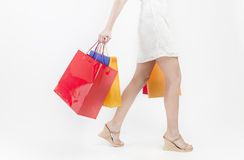 Shopping. Woman in white skirt walking and holding shopping bags royalty free stock photography