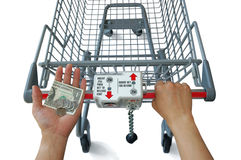 Shopping. Photo of isolated shopping cart being pushed by a person with money in other hand Royalty Free Stock Photography
